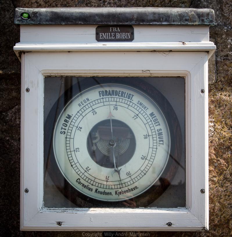 Barometeret på kaia viser at det er ustadig vær i vente. Barometeret har sitt opphav hos den velkjente Cornelius Knudsen i København. Instrumentene er verdenskjente, og firmaet har utstyrt mange store ekspedisjoner gjennom tidene.