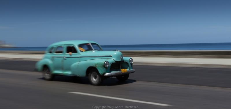 En klassisk amerikaner i flott driv langs strandpromenaden Malecon.