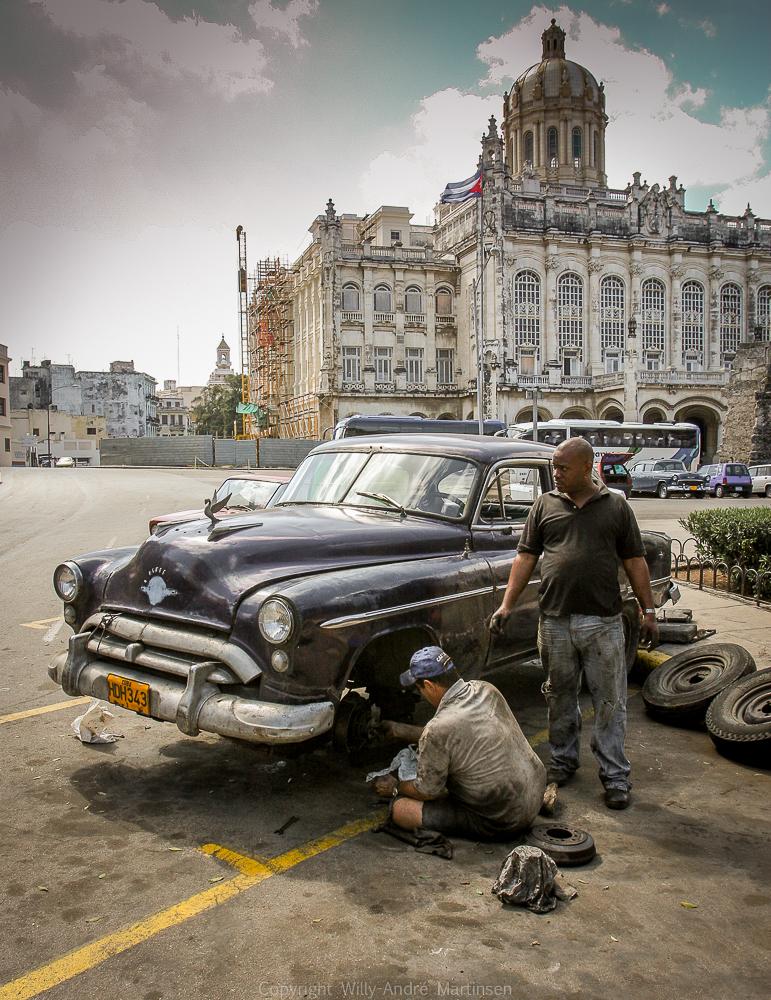 Kubanerne må reparere bilene på det stedet de bryter sammen. Disse to karene må fikse en brukket foraksling rett utenfor Capitolio i Havana sentrum.